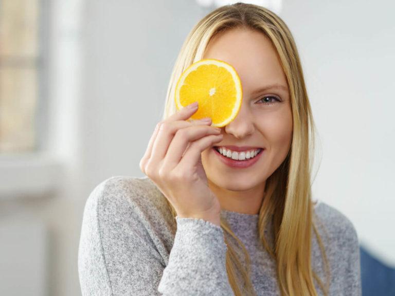 Junge lächelnde Frau hält Orangenscheibe in der Hand