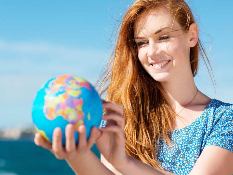 Junge rothaarige Frau hält Miniaturglobus in den Händen